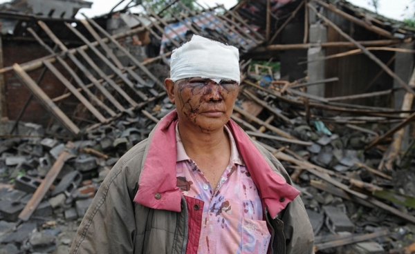 An injured man stands outside his destroyed home a day after a 7.8 magnitude earthquake hit the town of Hanwang in Sichuan Province. (Mark Ralston/AFP/Getty Images)