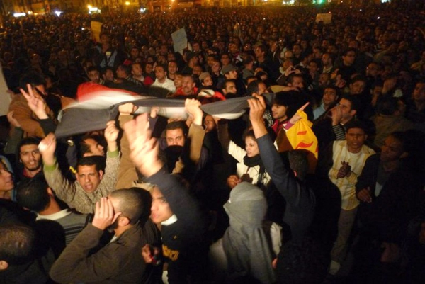 Egyptian protestors hold their national flag during demonstration in Cairo on January 25, 2011 demanding the ouster of President Hosni Mubarak (Al Jazeera).