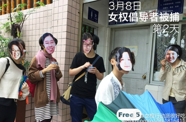 "Masked activists pose in front of a public restroom to commemorate the ""Occupy Men's Room"" movement that several of the detained feminists organized in 2012."