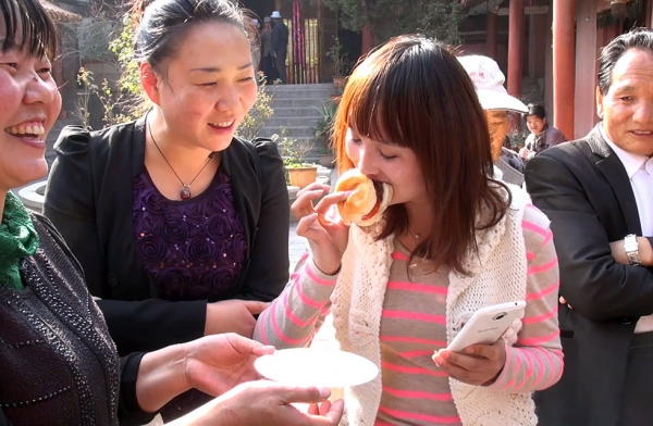 "A temple patron eats a veggie burger in ""Sauced in Translation"" episode 8 in Qujing, Yunnan, China. (Howie Southworth)"