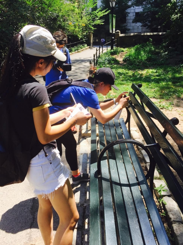 Young Scholar Dang Weikun takes a picture of a Central Park bench plaque while Young Scholar Liang Qiqi keeps track of all the bench plaques they have documented thus far. (Zhangbolong Liu & Zhu Xi/New York)