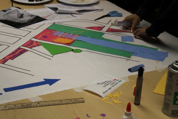Team members work on a large cut-paper conceptual layout of the site redesign