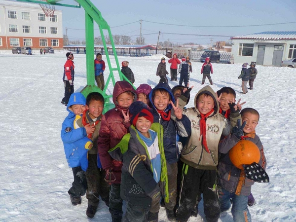 Wasteland's elementary students at recess in deep winter. The three-story school in the background was the tallest structure in Wasteland until the railway overpass was built. (Michael Meyer)