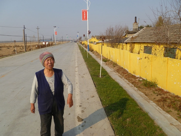 "A local named Auntie Yi stands on the improved Red Flag Road, which now features solar-powered streetlights and Wasteland's first ""lawn"" — a strip of ornamental sod. (Michael Meyer)"