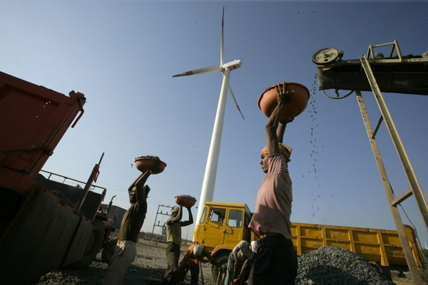 India Bundled Wind: A laborer is seen working at a deisel powered crusher infont of a wind turbine. (Land Rover Our Planet/Flickr)