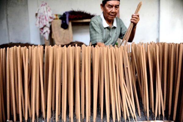 A man prepares incense sticks for drying in anticipation of increased orders for upcoming Lunar New Year festivities on January 18, 2014 in Malang, Indonesia. (Robertus Pudyanto/Getty Images)