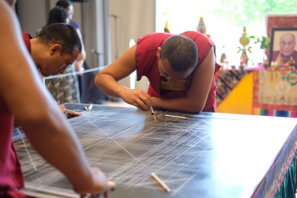 The monks draw an outline of the mandala on the wooden platform. (Jessica Ngo)