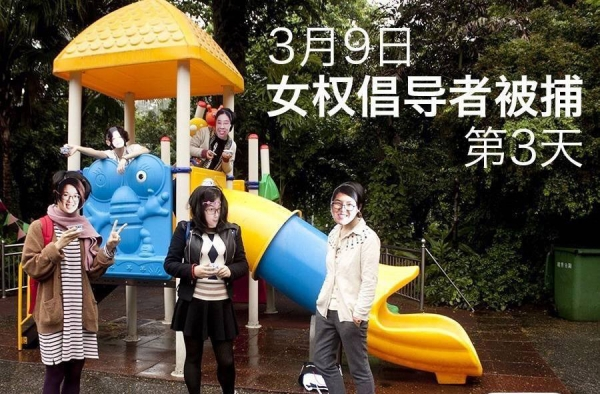 Masked activists pose on playground equipment.