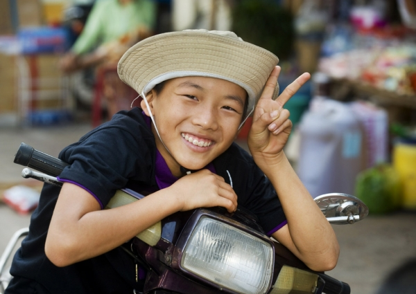 A friendly Vietnamese boy stops his bicycle in Cao Lahn, Vietnam to offer a smile and a peace sign on February 22, 2010. (Nancy A. Scherl)