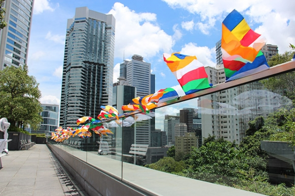 Nepalese prayer flags waving under bright sky on Joseph & Josephine Lau Roof Garden