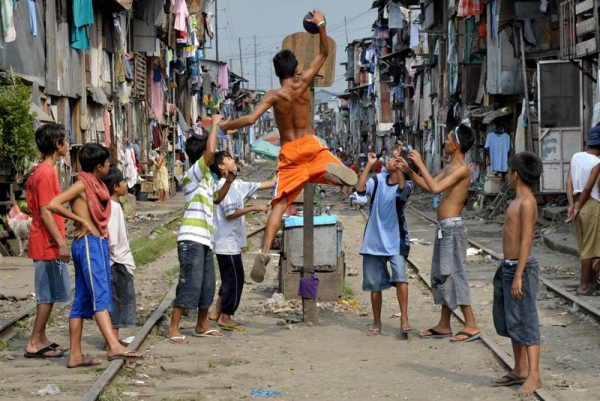 Children play basketball along railroad tracks bounded by shanty houses in Manila on March 12, 2008. (Jay Director/AFP/Getty Images)