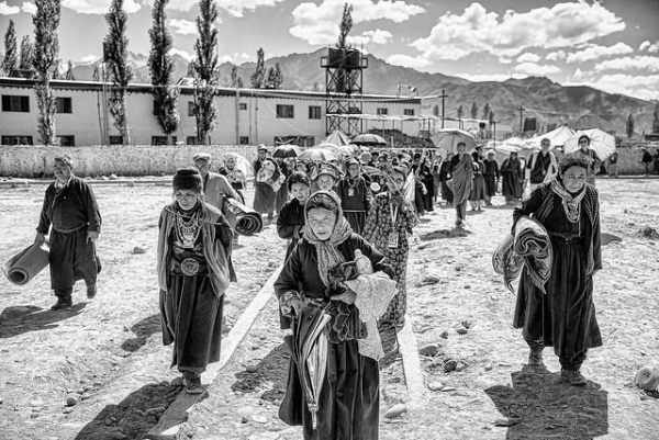 A large group of people trek carrying personal belongings through Ladakh, India on July 10, 2014. (Christopher Michel/ Flickr)