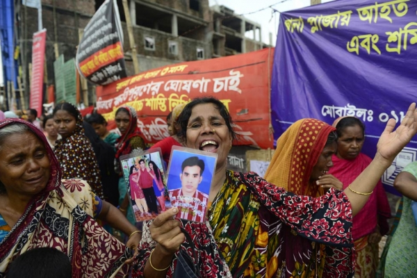 A mourner holds pictures of a relative lost in the collapse of Rana Plaza in Bangladesh on April 24, 2013, considered the deadliest accidental structural failure in human history. (Munir Uz Zaman/AFP/Getty Images)