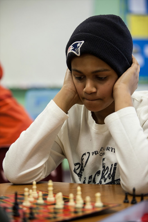 Middle school students concentrating on a chess game. Middle and high school students have an array of activities and clubs to participate in to complement their academic studies.
