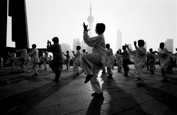 A group of people perform Tai Chi in the morning on the banks of the Huang Pu River in Shanghai. (Ryan Pyle)