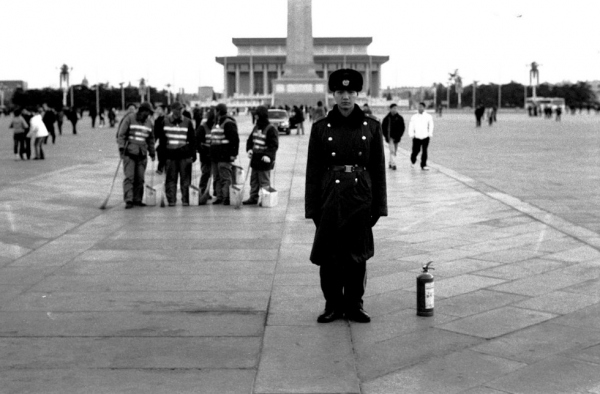 A solider stands next to a fire extinguisher in Tiananmen Square in Beijing. The irony is that everything there is made of stone. (Ryan Pyle)