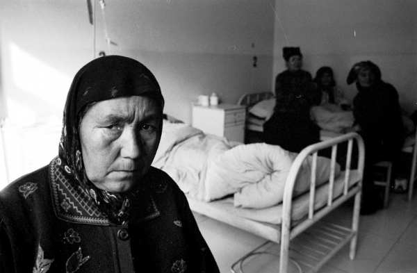 A cataract patient sits in her hospital room before her surgery in Khotan. (Ryan Pyle)