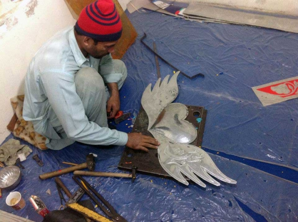 A rickshaw artist hammers out a design on a metal ornament. (Pakistan Youth Alliance)