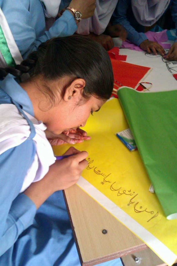 "A young student decorates a panel with a slogan during the ""Peace-building Thru Artistic Expressions"" workshop. (Pakistan Youth Alliance)"
