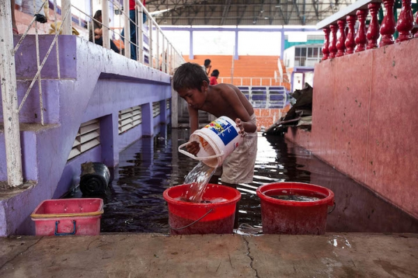 A child scoops water out of the flooded sports complex in Medellin, Bogo in the aftermath of Typhoon Yolanda.