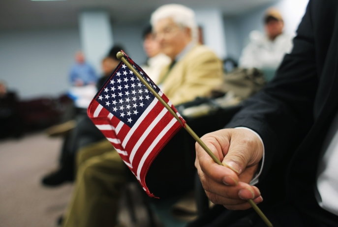An immigrant from India holds a flag while waiting for a naturalization ceremony to become a U.S. citizen