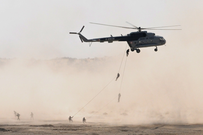 Indian and U.S. soldiers rappel from an Indian Air Force helicopter for military exercise