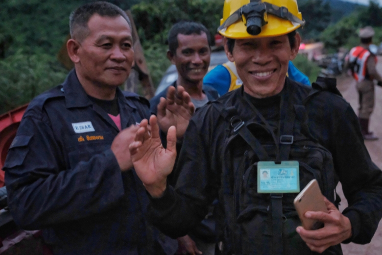 A rescuer at Thailand's Tham Luang cave complex smiles during an operation to rescue 12 boys and their soccer coach.