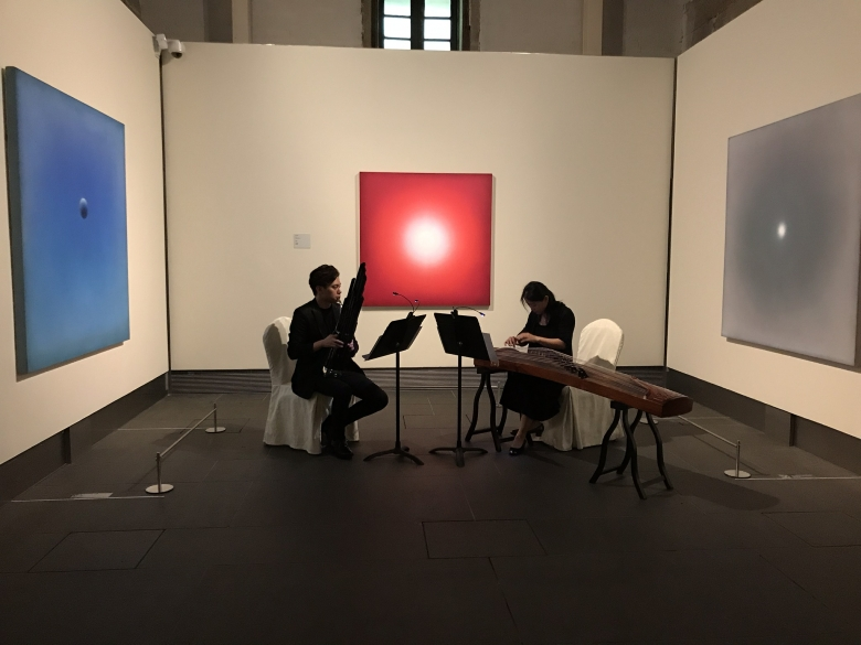 Musicians playing in an art gallery.