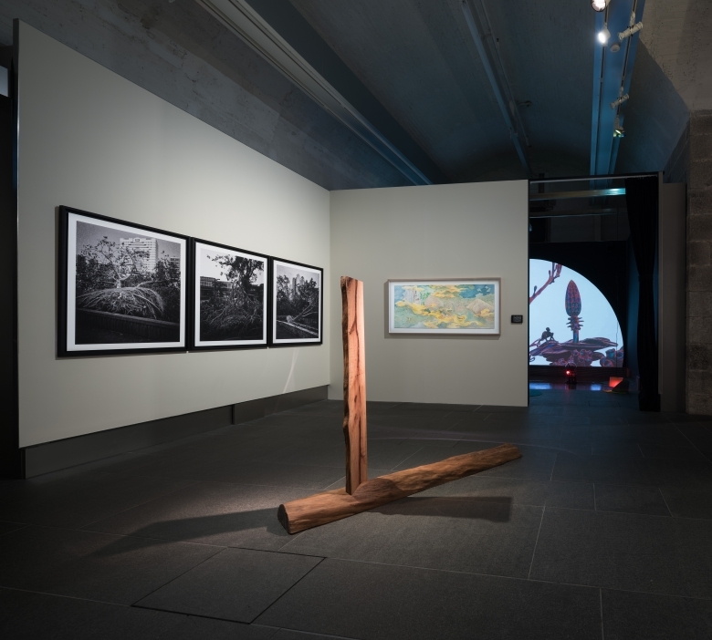 Two black and white photographs on the wall, a wooden sculpture in the center of the floor, and an animated artwork in the back.