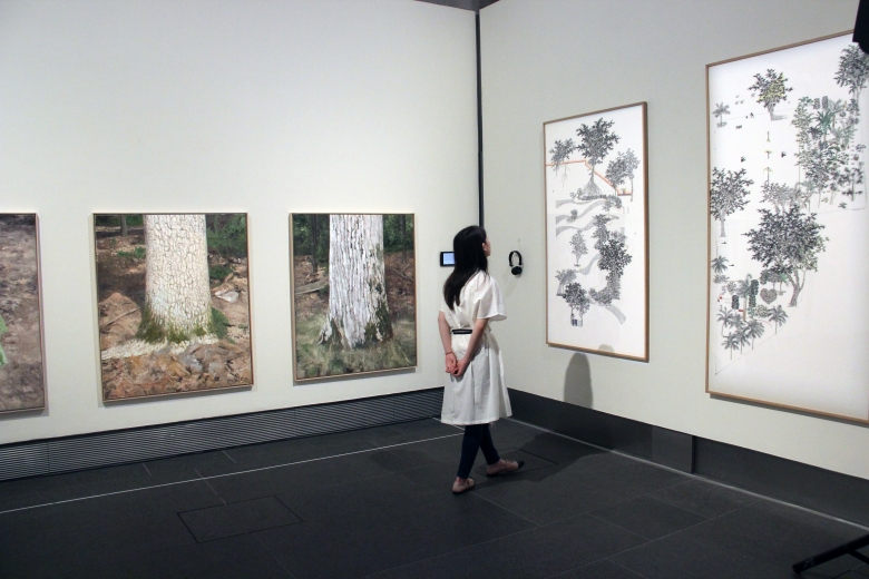 Visitor next to Natee Utarit's paintings of oak tree trunks (left) and looking at Frank Tang's Pocket Park series of paintings (right)