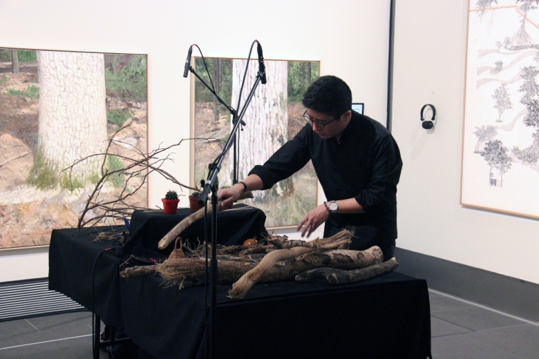 Man playing branches as an instrument in a gallery
