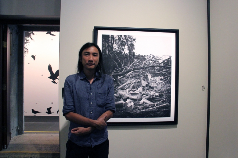 Participating artist South Ho standing next to a work from his Whiteness of Trees (2018) photograph series.