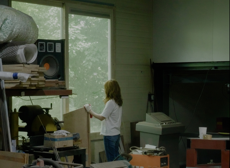 A person stands in an artists studio, looking out a window. She wears a white t-shirt, jeans, and white gloves. Lumber, cups, and boxes appear around her.