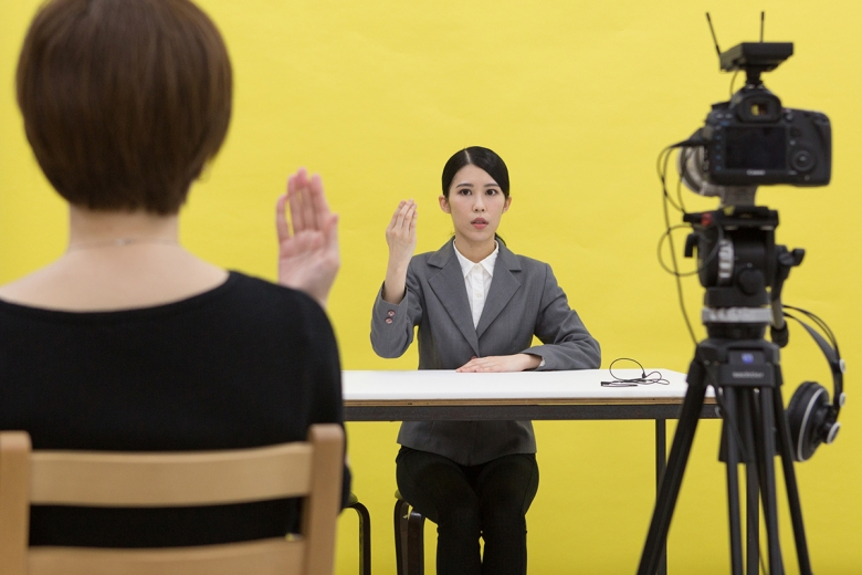 A person sits at a bare table, wearing a white-button down shirt and gray blazer. Her right hand is raised, the back of her hand facing the viewer. Another person sits across from her, also raising their right hand. They sit in front of a yellow background, and a video camera on a tripod appears at the right.