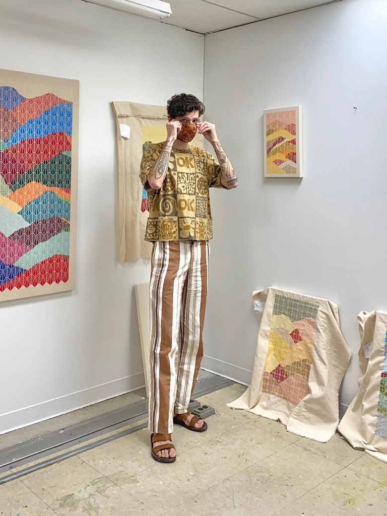 Jordan Nassar stands in his studio wearing patterned clothes and facemask. He is surrounded by his embroidered works.