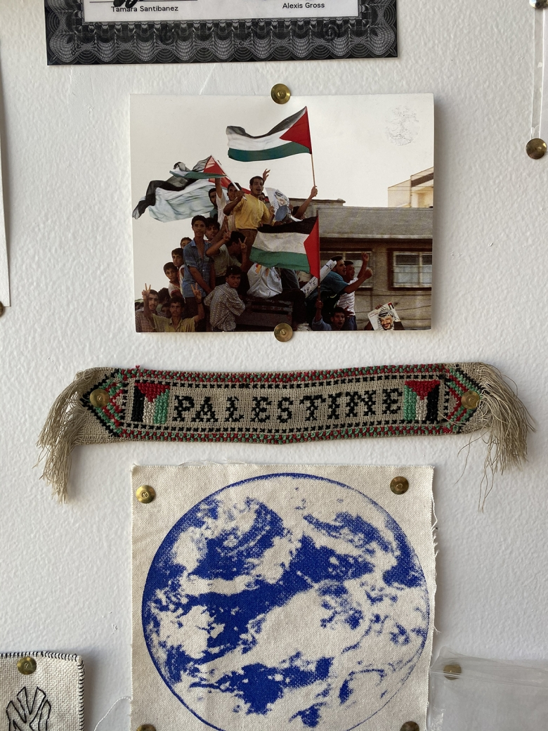 "Items are tacked to a white wall including a photograph of people waving Palestinain flags, a small piece of embroidery that includes the word ""Palestine,"" and a blue drawing of the Earth."