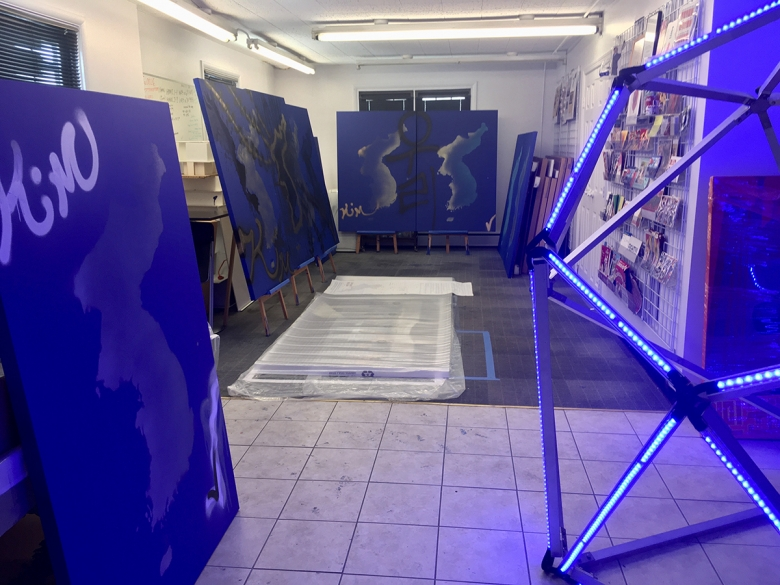 A series of large, blue canvasses are propped on easels around a tile-floored room. A bright, electric, blue sculpture appears at the right.
