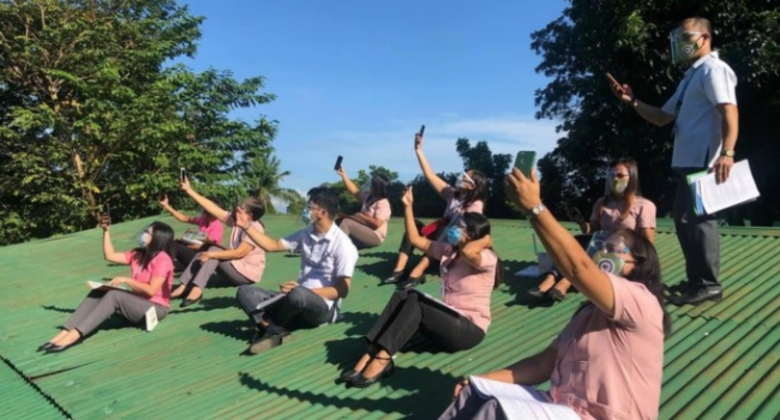 Teachers in uniform on top of rooftop with their hands with phones reaching out