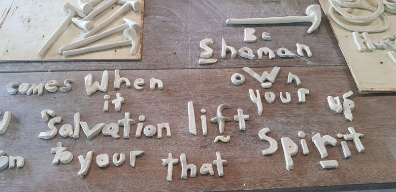 Letters made of clay appear on a wood tablet, spelling out words: Be, shaman, comes, when, own, it, salvation, lifts, your, up, to your, that, and spirit. Several hammers made of clay are on the table, as well.
