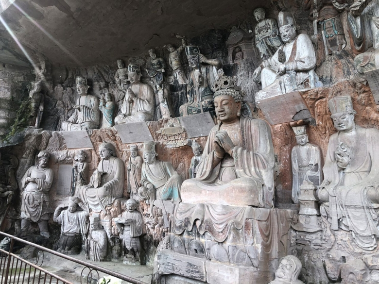 A couple dozen stone figureative sculptures are arranged on on tiers cut into a rock wall. Most appear to be religious in nature
