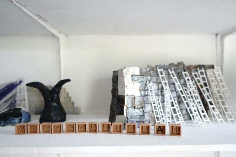 Small objects appear on a white shelf include several box-shaped pieces inscribed with a letter, miniature ladders, a black clay piece with a forked top, and black, white, and silver stacked blocks.