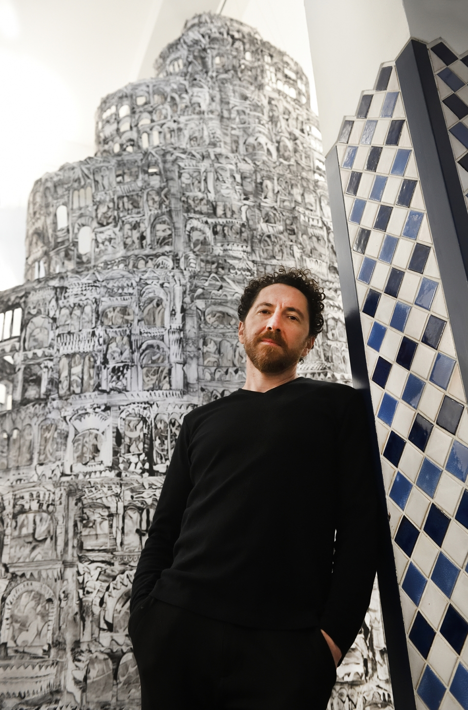 A man with a beard dressed in black stands in front of an elaborate drawing of a tower